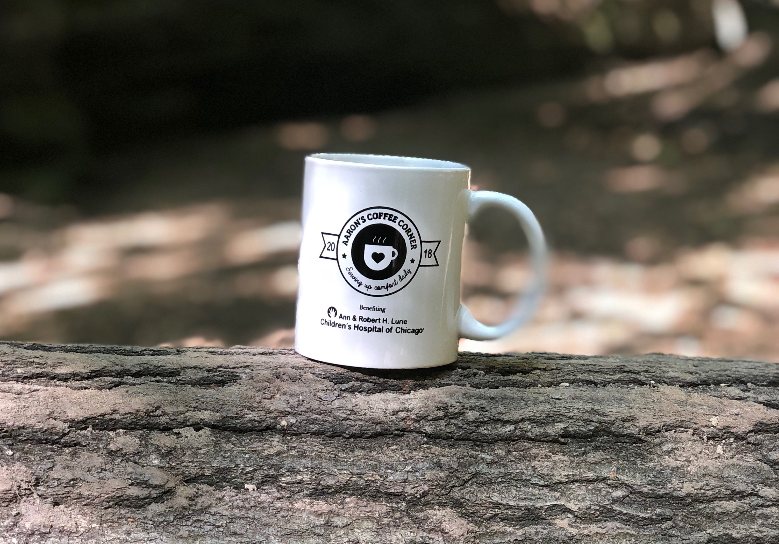 Background photo of an Aaron's Coffee Corner mug on a log in nature
